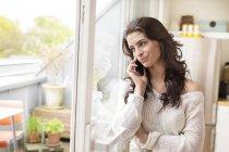 Улыбающаяся молодая женщина на телефоне у окна — стоковое фото