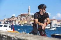 Croatia, Istria, Rovinj, racing cyclist having a break at the harbor — Stock Photo