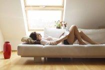 Розслабленої жінка, лежачи на дивані, використовуючи ноутбук — стокове фото