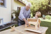 Großvater und Enkel bauen Vogelhäuschen — Stockfoto