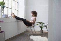 Donna che si siede nella sedia utilizza la compressa di digital — Foto stock