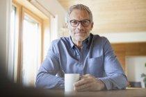 Porträt von zuversichtlich reifer Mann mit Tasse am Tisch — Stockfoto