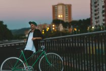 Smiling man with bicycle leaning against railing at dusk — Stock Photo