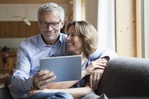 Mature couple sharing digital tablet on couch — Stock Photo