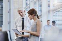Uomo d'affari e donna di affari con la compressa digitale in ufficio moderno — Foto stock