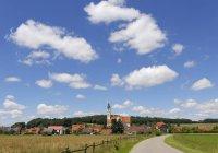 Alemania, Baden-wurttemberg, Swabia, vistas al antiguo pueblo con torre de la iglesia por los verdes campos - foto de stock