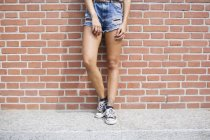 Partial view of young woman in jeans shorts and sneakers — Stock Photo