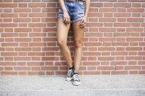 Часткове зору того, молода жінка в джинсах шорти і кросівки — стокове фото
