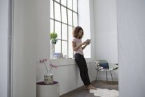 Young woman standing at the window using digital tablet — Stock Photo