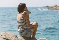 Vue arrière de la jeune femme avec des vêtements d'été regardant la mer assise sur la côte rocheuse — Photo de stock