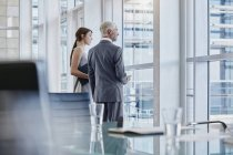 Two business people looking out of the window — Stock Photo