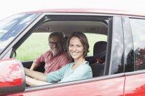 Porträt eines glücklichen, reifen Paares zusammen im Auto — Stockfoto