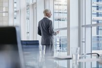 Businessman looking out of the window in the office — Stock Photo