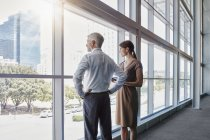 Two business people looking out of a big window — Stock Photo