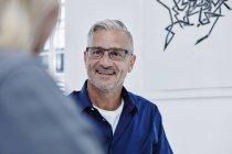 Uomo d'affari sorridente in un incontro in un ufficio moderno — Foto stock
