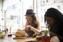 Друзья сидят в кафе, едят сэндвичи — стоковое фото
