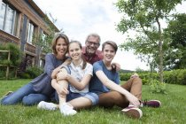 Portrait of happy family sitting in garden — Stock Photo