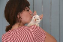 Woman wearing spectacles holding kitten — Stock Photo