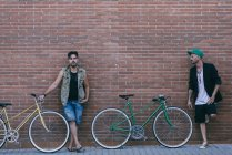 Two men with vintage bicycles leaning against brick wall — Stock Photo