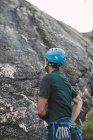Vista posteriore di Climber alzando lo sguardo sulla parete rocciosa — Foto stock