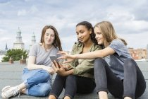 Germany, Berlin, three teenage girls sitting on roof top listening music with earphones — Stock Photo