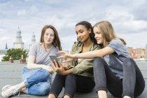 Німеччина, Берлін, трьох дівчат-підлітків сидячи на покрівлі верхній прослуховування музики з навушники — стокове фото