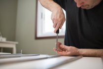 Man using screwdriver for assembling furniture at home — Stock Photo