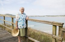 Heureuse femme âgée debout sur la promenade — Photo de stock