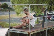 Smiling skateboarder using smartphone in skatepark — Stock Photo
