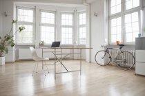 Computador portátil na mesa no escritório esparsa — Fotografia de Stock