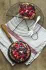 Due tortine di crosta con bacche e crema su legno con porta raffreddamento e strofinaccio da cucina — Foto stock