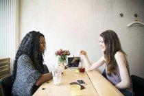 Две молодые женщины, имеющие встреча в кафе — стоковое фото