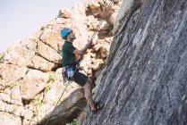 Young man climbing on rock wall — Stock Photo