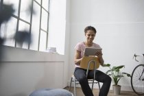 Woman sitting in chair using digital tablet — Stock Photo