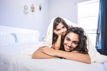 Portrait of teenage girl and her little sister sitting lying on bed under a blanket — Stock Photo