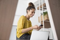 Smiling woman sitting on office desk using cell phone — Stock Photo