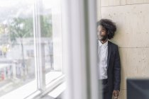 Young businessman standing by window, thinking — Stock Photo