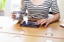 Primo piano della donna che tiene tazza di caffè con il ridurre in pani digitale — Foto stock
