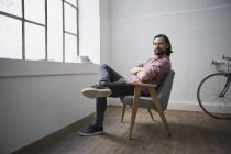 Man sitting in chair with arms crossed at home — Stock Photo