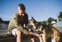 Улыбающийся человек, поглаживая собаку в скейтпарк — стоковое фото