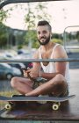Porträt von lächelnden Skateboarder mit smartphone — Stockfoto