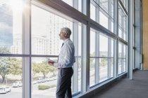 Geschäftsmann aus einem großen Fenster im Büro — Stockfoto