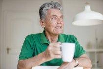 Sorrindo homem sênior em casa segurando xícara de café — Fotografia de Stock