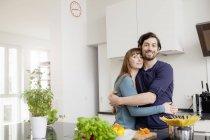 Porträt eines glücklichen Paares, das sich in der Küche umarmt — Stockfoto