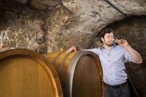 Homem degustação de vinho na adega — Fotografia de Stock