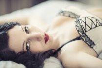 Молодая женщина в нижнем белье лежит на кровати — стоковое фото