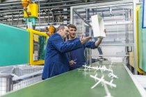 Менеджер і працівник робить якість оцінки в пластмаси заводу — стокове фото