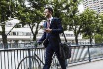 Homme d'affaires avec vélo marchant dans la ville et tenant smartphone — Photo de stock