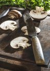 Sliced brown button mushroom with knife on wooden chopping board — Stock Photo
