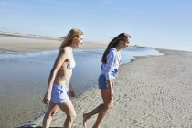 Two female friends walking together on beach — Stock Photo